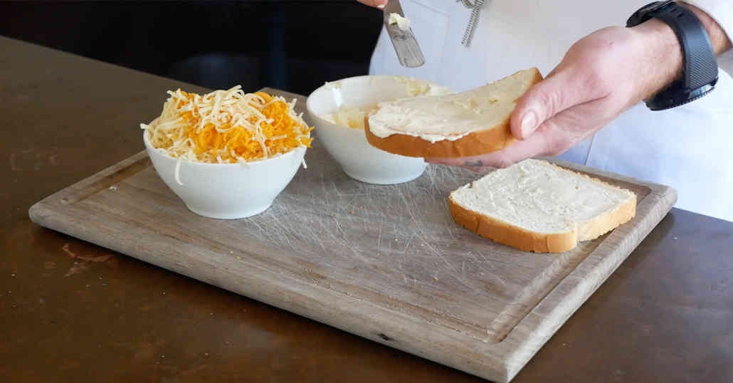 Buttered Bread with Cup of Cheese on Board