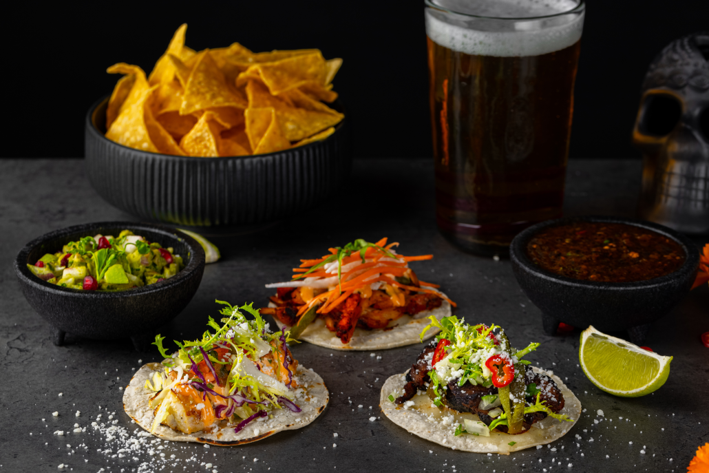 Taco trio with chips, dip, and beer