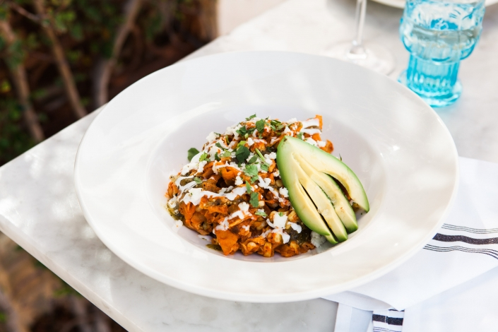 chilaquiles with avocado on a table