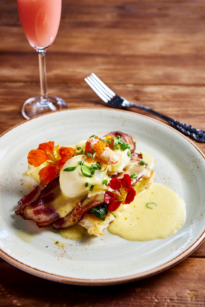 Eggs Benedict with glass of wine