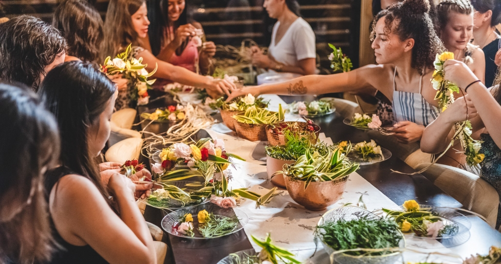 Ladies around a table making leis with fresh flowers and greens