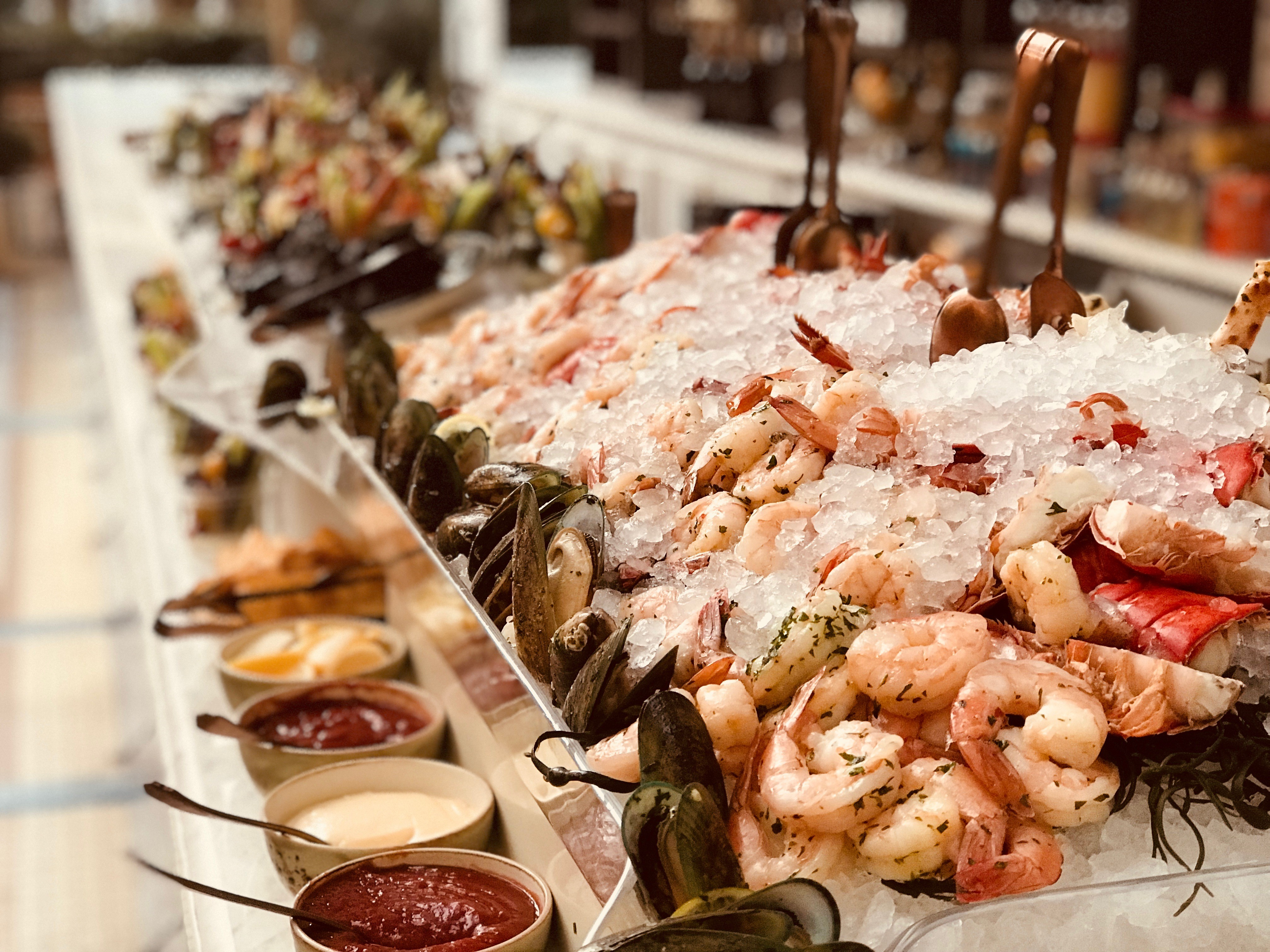 Seafood spread over ice with various dipping sauces