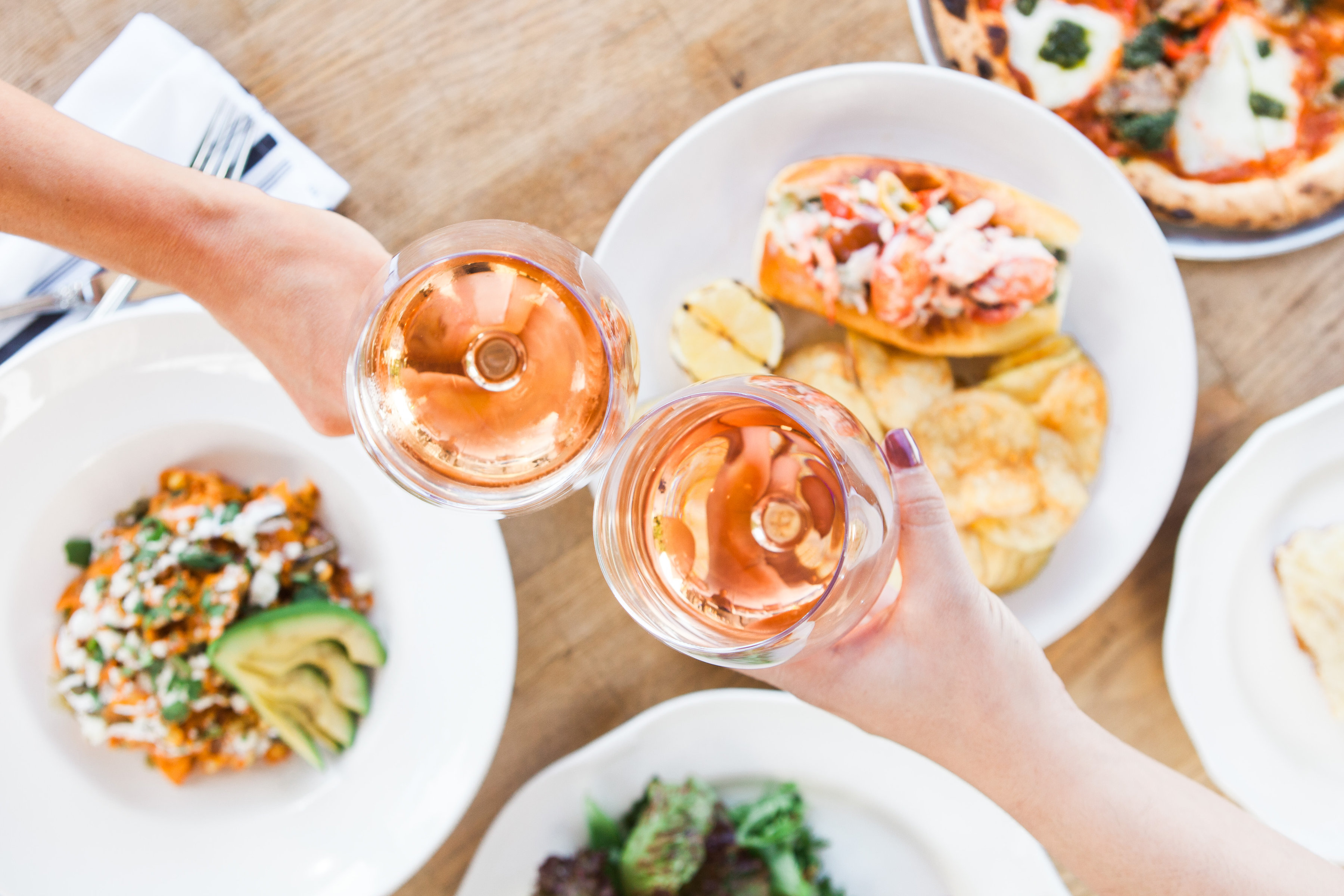 Two glasses of rose toasting over several dishes