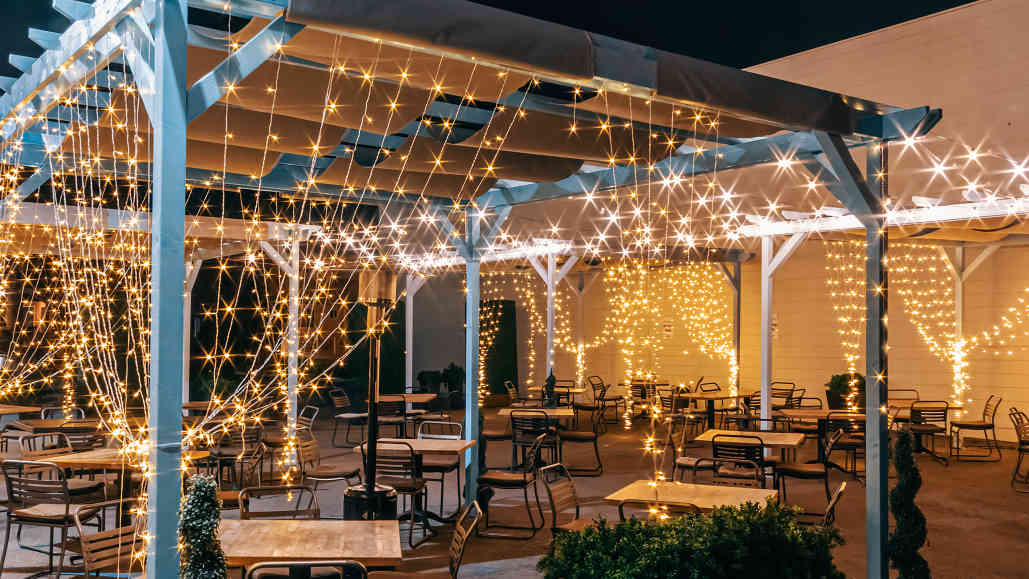 Herringbone La Jolla's outdoor dining area at night with sparkling lights.